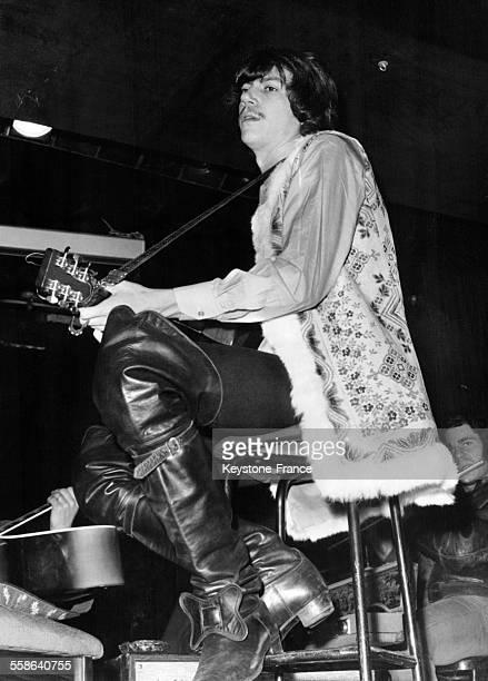 Le chanteur Antoine cheveux presque courts vêtu d'une veste hippie et portant d'immenses bottes de mousquetaire en pleine répétition au cabaret 'La...