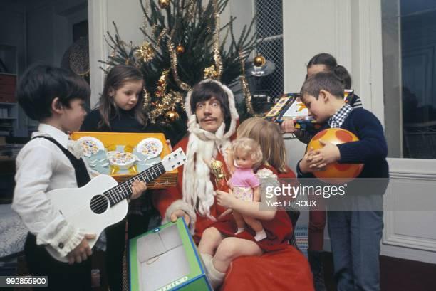 Le chanteur Antoine déguisé en Père Noël avec des enfants autour d'un sapin circa 1970 France
