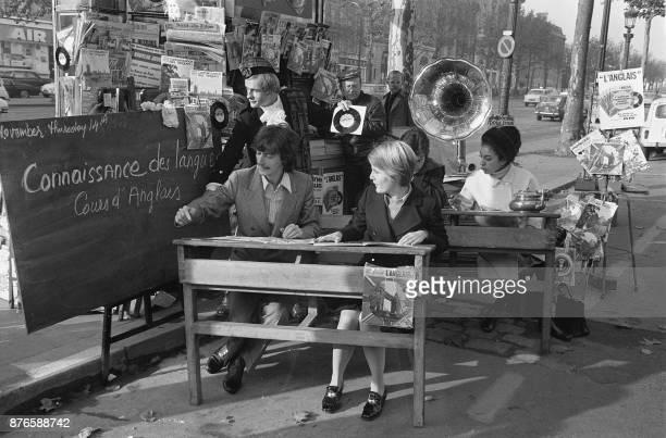 Le chanteur Antoine est assis à un pupitre d'école à l'occasion du lancement d'une nouvelle méthode de langues vivantes sur l'avenue des champs...