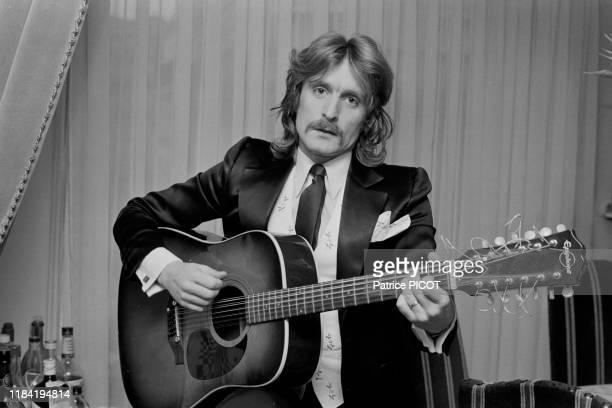 Le chanteur Christophe avec une guitare hez lui à Paris le 11 février 1974, France.