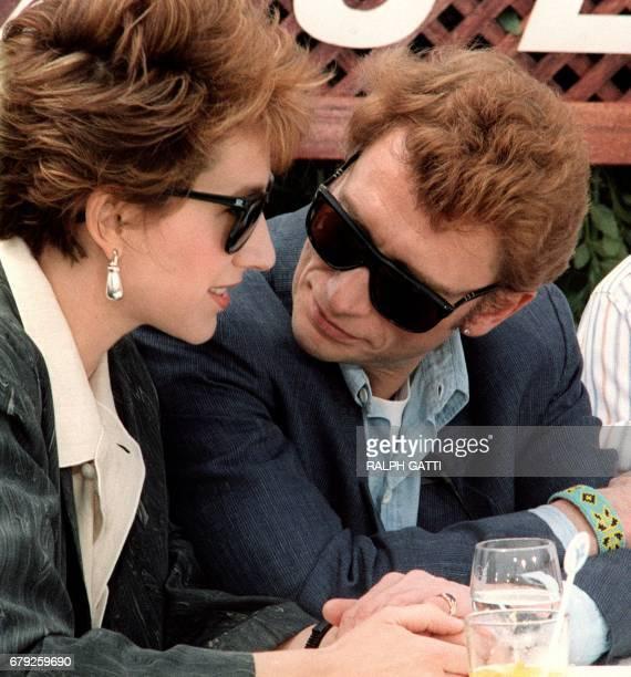 Le chanteur de rock et acteur français Johnny Hallyday s'entretient le 10 mai 1985 avec son amie l'actrice française Nathalie Baye lors de la...