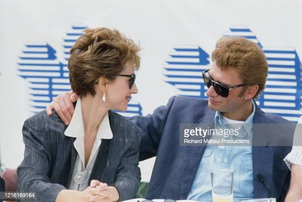 """Le chanteur et acteur Johnny Hallyday et sa compagne l'actrice Nathalie Baye, au 37ème Festival de Cannes, sont venus présenter le film """"Détective""""..."""
