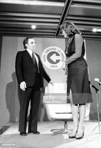 Le chanteur français Charles Aznavour et l'actrice américaine Raquel Welch lors d'une conférence de presse à Paris en France le 4 février 1976
