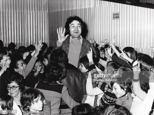 Le chanteur français Pierre Perret au milieu d'une foule d'enfants.