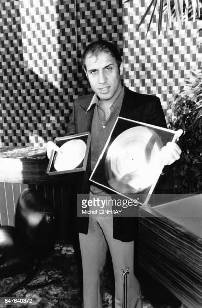 Le chanteur italien Adriano Celentano pose avec ses 2 disques d'Or en decembre 1977 Paris France