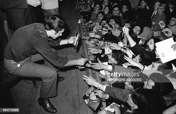 Le chanteur italien Salvatore Adamo signant des autographes à ses fans lors d'un concert.