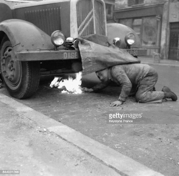 Le chauffeur de ce camion allume un feu sous le moteur pour le dégeler à Paris France le 2 février 1956