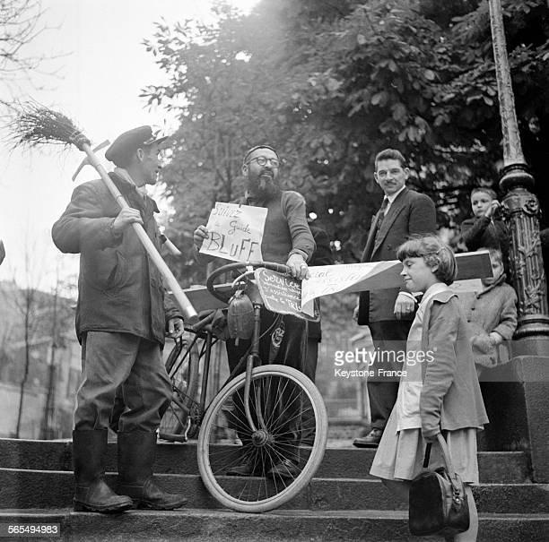 Le chef de la tribu des 'Aiguiguistes' assis sur un vélo qu'il a conçu tient dans ses mains une pancarte annonçant le lancement du nouveau service...