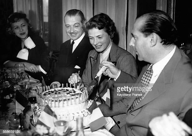 Le cinéaste italien Roberto Rosselini coupe son gâteau d'anniversaire en compagnie de son épouse Ingrid Bergman et de leurs amis Fernand Gravey et...