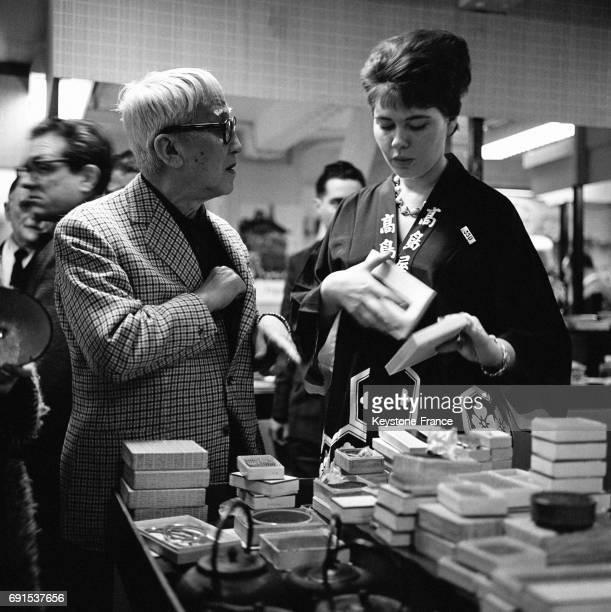Le célèbre peintre Foujita achète des produits à une vendeuse portant pour la circonstance le costume japonais au grand magasin du Louvre à Paris...