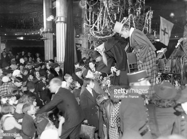 Le clown Bilboquet et le Père Noël distribuant des jouets lors de l'arbre de Noël des enfants à Paris France en décembre 1934