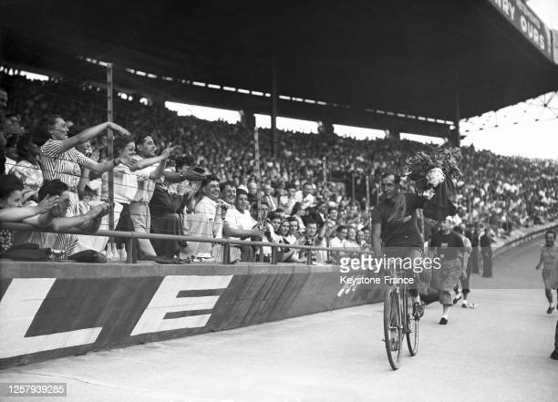 Le coureur italien Gino Bartali célébrant sa victoire dans la compétition lors de son arrivée au Parc des Princes à Paris lors de la dernière étape...