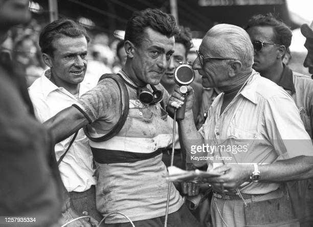 Le coureur italien Gino Bartali interrogé par des journaliste au Parc des Princes après sa victoire au Tour de France à Paris le 25 juillet 1948...