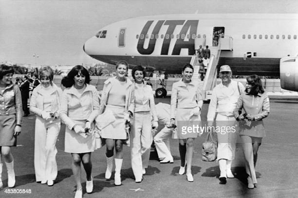 Le couturier André Courrèges marche sur la tarmac avec ses mannequins après avoir débarqué du DC10 à bord duquel il a présenté les nouveaux uniformes...