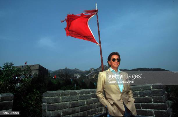 Le couturier italien Valentino Garavani pose devant un drapeau chinois sur la Muraille de Chine en mai 1993 Chine