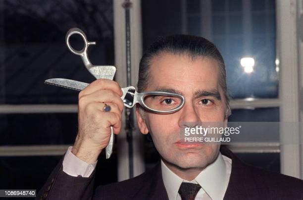 Le couturier Karl Lagerfeld pose avec une paire de ciseaux en mars 1987 dans son atelier de haute couture German designer Karl Lagerfeld poses with...