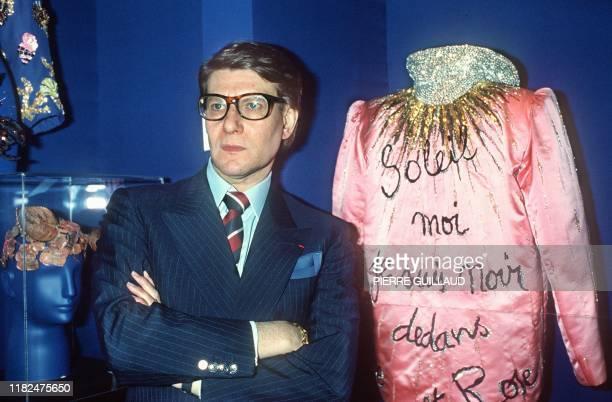 Le couturier Yves Saint Laurent pose le 25 juillet 1984 à Paris devant l'une des ses créations lors de la présentation de sa collection automne-hiver...