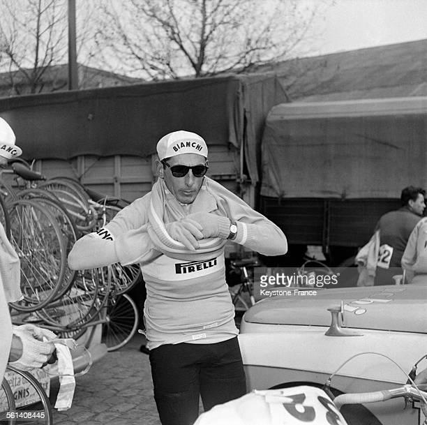Le cycliste italien Fausto Coppi enfile des vêtements chauds à la Porte de Versailles avant le départ de la course ParisNice le 10 Mars 1958 à Paris...