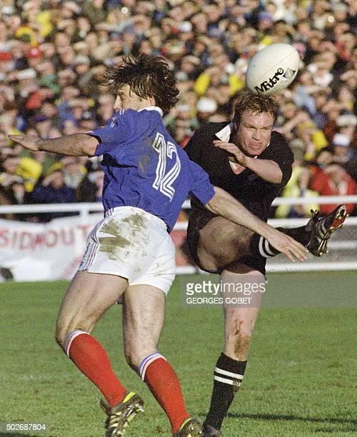 le demi d'ouverture néozélandais Grant Fox dégage le ballon sous la pression du troisquarts centre français Denis Charvet le 20 juin 1987 à l'Eden...