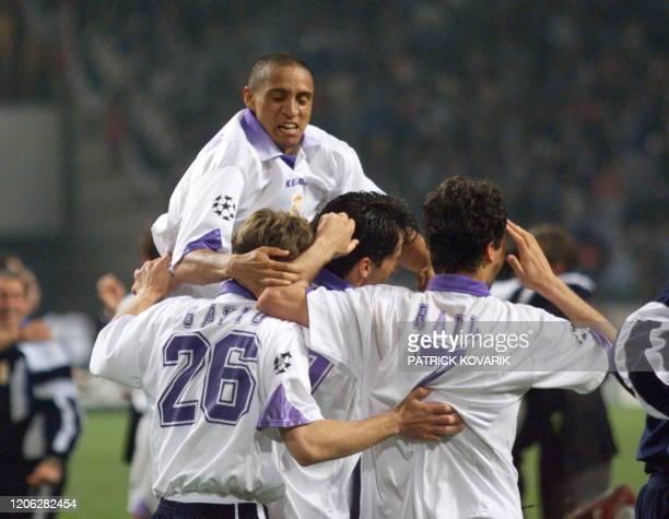 Le défenseur brésilien du Real Madrid, Roberto Carlos, saute de joie sur ses coéquipiers après avoir remporté avec son équipe, le 20 mai à l'ArenA...