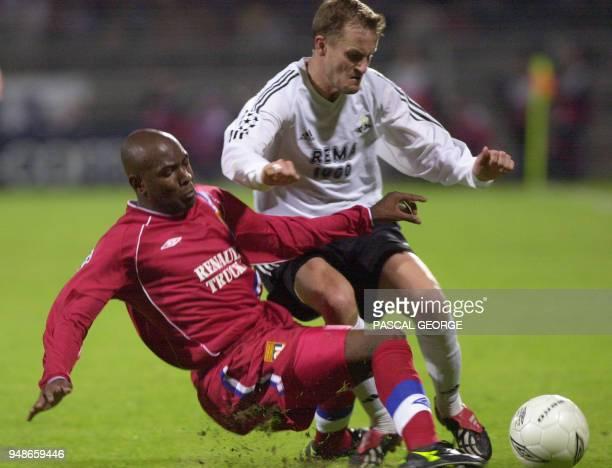 le défenseur lyonnais Claudio Caçapa tente de tacler le norvégien Harald Martin Brattbakk le 25 Septembre 2002 au stade Gerland à Lyon lors du match...