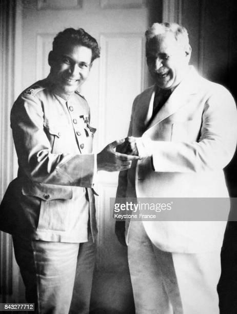 Le dictateur cubain Batista examine en riant la main égratignée du président Mendieta après l'attentat à la bombe qui a tué deux marins le 18 juin...