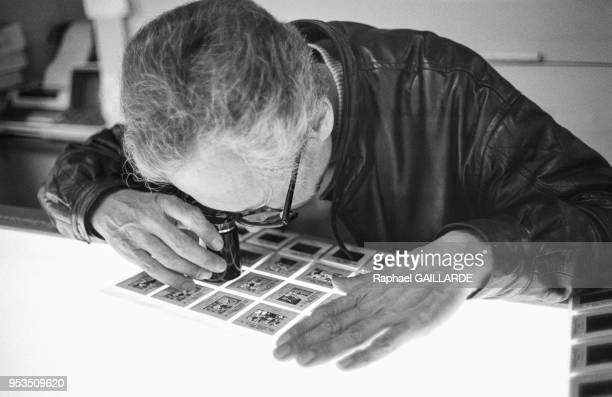 Le directeur de l'agence Gamma Jean Monteux regarde des photos couleur à l'aide de son comptefil sur une table lumineuse en juin 1986 à Paris France