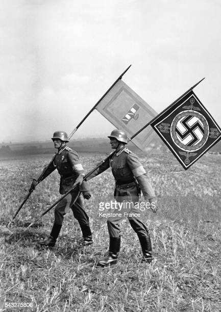 Le drapeau de l'Italie fasciste de Mussolini et celui de l'Allemagne nazie de Hitler sont portés par deux soldats durants une manoeuvre militaire le...