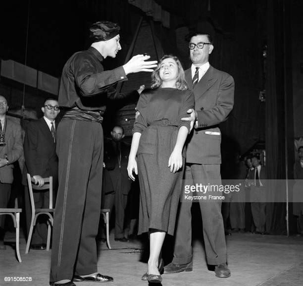 Le fakir Karmah hypnotise une jeune femme sur scène au Théâtre de l'Etoile à Paris France le 22 octobre 1954