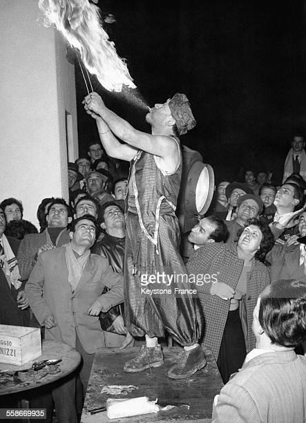 Le fakir Reno Tenca cracheur de feu dans un numéro en plein air en Italie le 17 janvier 1956