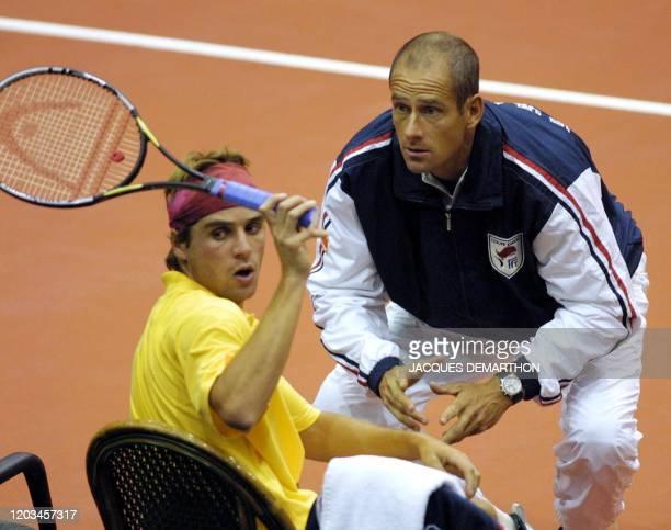 le Français Arnaud Clément donne sa raquette à un technicien alors qu'il s'entretient avec son capitaine Guy Forget le 21 septembre 2001 à Rotterdam...