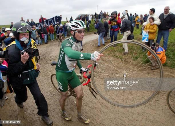 Le Français Christophe Jenher tend sa roue après avoir crevé, le 14 avril 2002 lors de la 100e édition de la classique cycliste Paris-Roubaix, 3e...