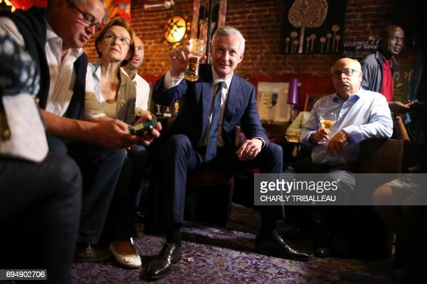 Le French Minister of Economy and parliamentary candidate Bruno Le Maire raises a glass after polls closed for the first round of the French...