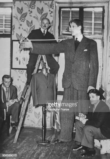 Le géant finlandais Myllyrinne de 2m45 se fait faire un costume surmesure chez un tailleur qui est obligé de monter sur une échelle pour prendre ses...