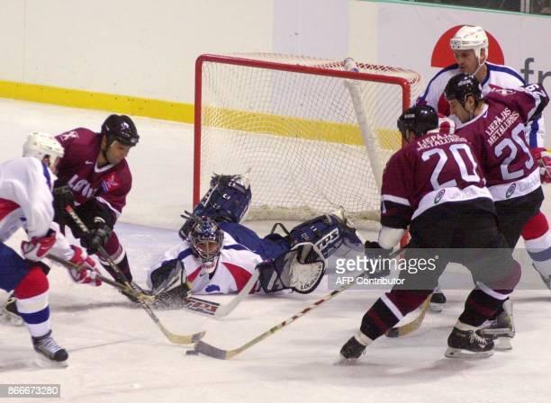 le gardien de but français Christobal Huet plonge pour stopper la palet face à l'attaquant letton Haris Vitolins le 09 novembre 2001 à Grenoble lors...