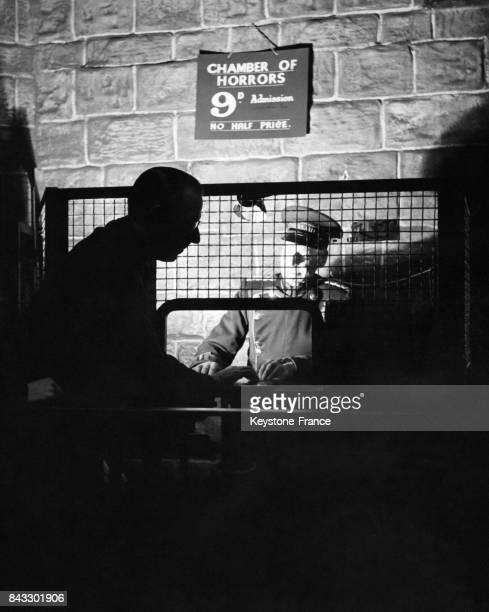 Le gardien de la 'Chambre des Horreurs' Harry Willett donne un ticket au dernier visiteur de la journée au musée de Mme Tussaud à Londres RoyaumeUni