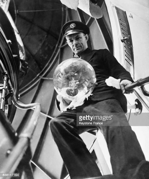 Le gardien du phare tenant dans la main une ampoule qu'il doit changer à Pendeen RoyaumeUni en 1946
