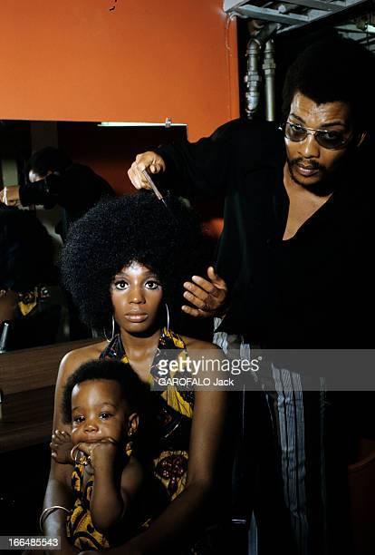 The Ghetto New York City Harlem juillet 1970 le ghetto le coiffeur et sa cliente assise tenant son enfant dans le salon de coiffure