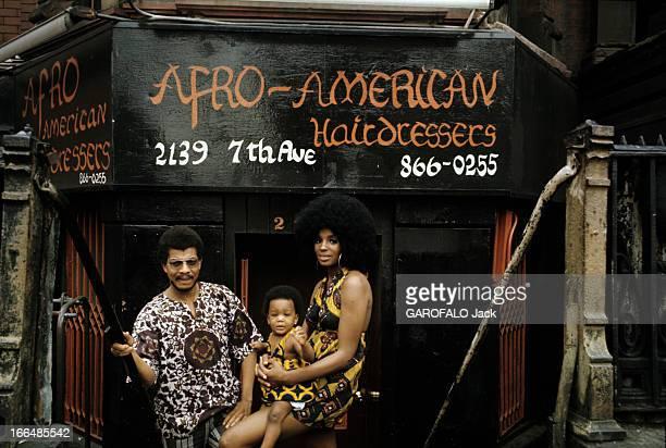 The Ghetto New York City Harlem juillet 1970 le ghetto une jeune femme afroaméricaine portant une perruque 'dernier cri' porte son enfant coiffé...