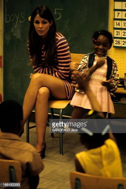 The Ghetto New York City Harlem juillet 1970 le ghetto une jeune institutrice 'blanche' en minirobe parmi ses élèves afroamréicains dans la salle de...