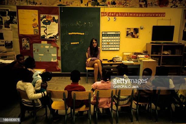 The Ghetto New York City Harlem juillet 1970 le ghetto une jeune institutrice 'blanche' en minirobe parmi ses élèves afroaméricains dans la salle de...
