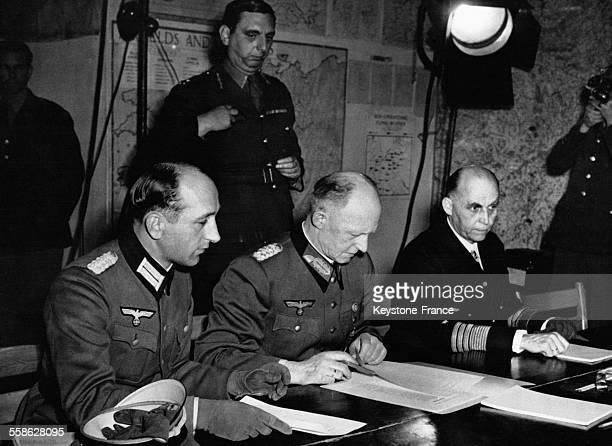 Le général Alfred Jodl signant l'acte de capitulation allemande à sa gauche le général Whilhelm Oxenius et à sa droite l'amiral HansGeorg von...
