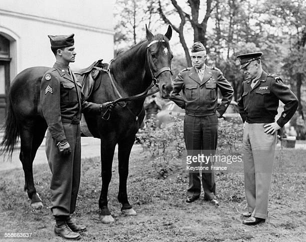 Le Général Bradley montre au Général Eisenhower le cheval, tenu par un soldat, que lui a offert le Maréchal Koniev, à Torgau, Allemagne, en 1945.