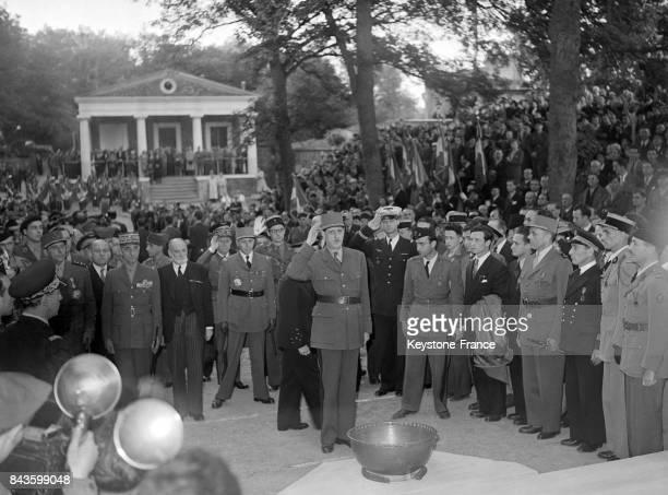 Le Général de Gaulle fait le salut militaire devant le flambeau allumé par l'Amiral d'Argenlieu au MontValérien lors d'une cérémonie célébrant...