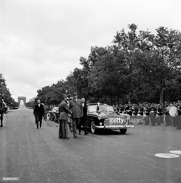 Le Général de Gaulle Président de la République marchant à côté de la voiture officielle sur les ChampsElysées à Paris France le 14 juillet 1961