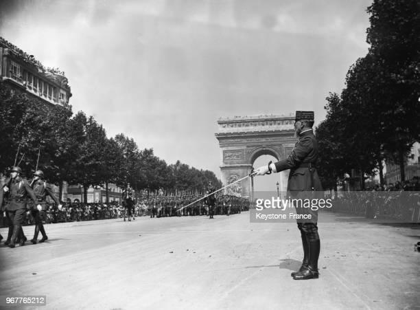 Le général Gouraud saluant les troupes défilant avenue des ChampsElysées à Paris France le 14 juillet 1935