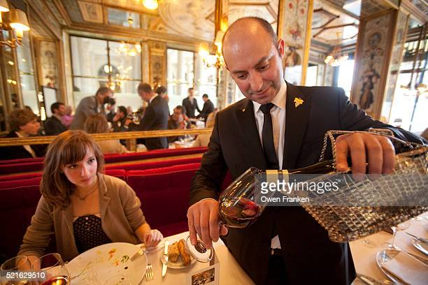 le grand vefour restaurant, paris - wine steward pouring red wine for a young diner - palais royal stock pictures, royalty-free photos & images