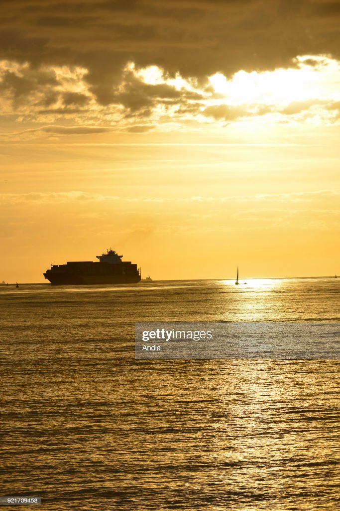 Le Havre (Normandy region, north western France): container ship and sailboat off the coast at sunset.