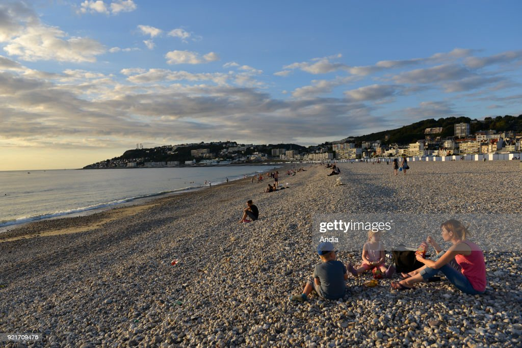 Le Havre (Normandy region, north western France): families on the pebble beach enjoying the sunset.
