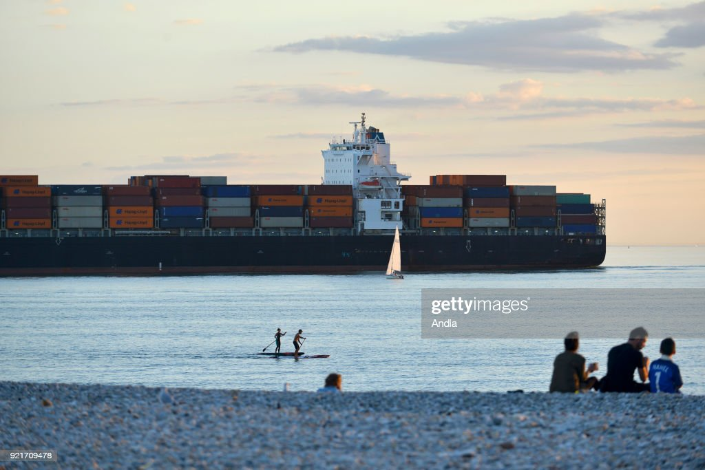 Le Havre (Normandy region, north western France): family on the beach, two stand up paddle boarders and container ship off the coast sailing back to the port.